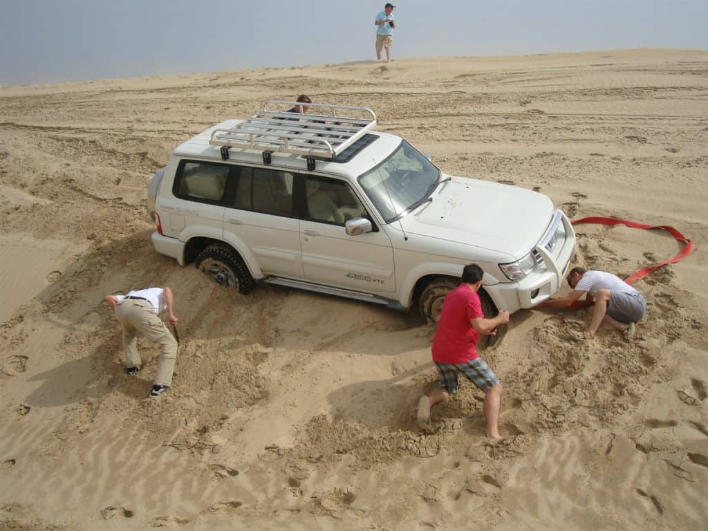 men sweeping sand from car